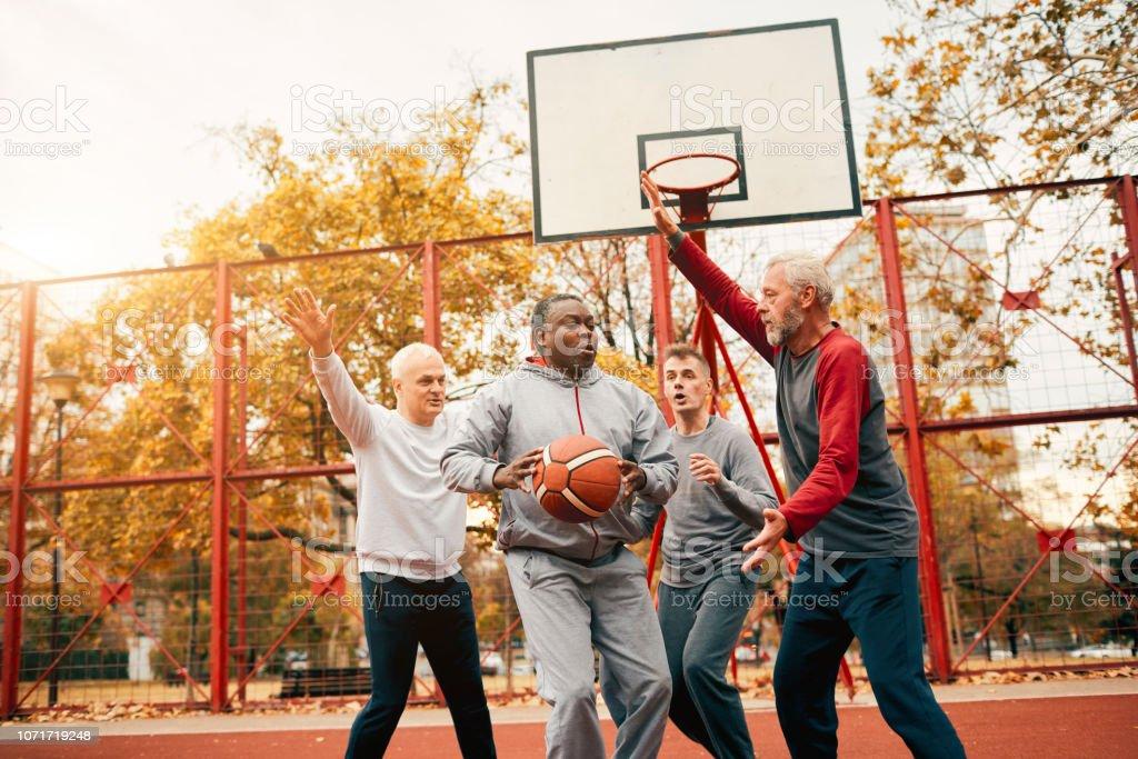 Group of Senior Men Basketball Outdoors in Public Park.