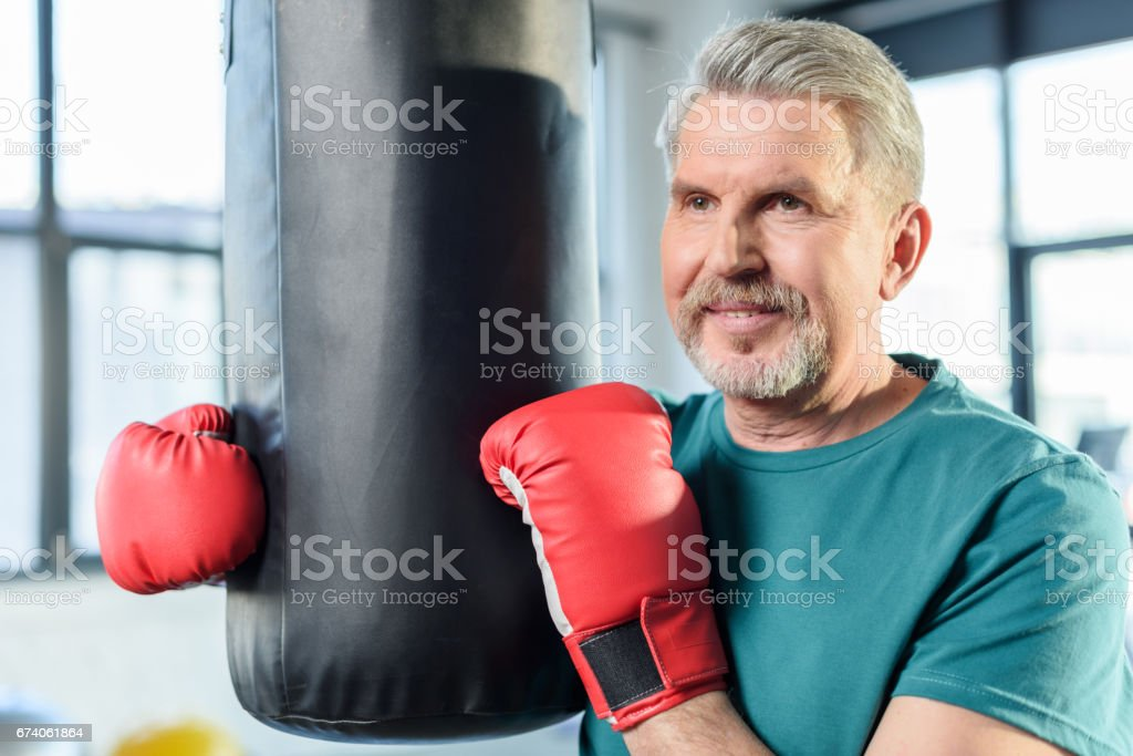senior sportsman in red boxing gloves with punching bag in fitness class royalty-free stock photo