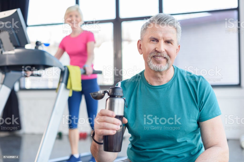 senior sportsman sitting with sport bottle, sportswoman on treadmill behind. senior fitness class concept royalty-free stock photo