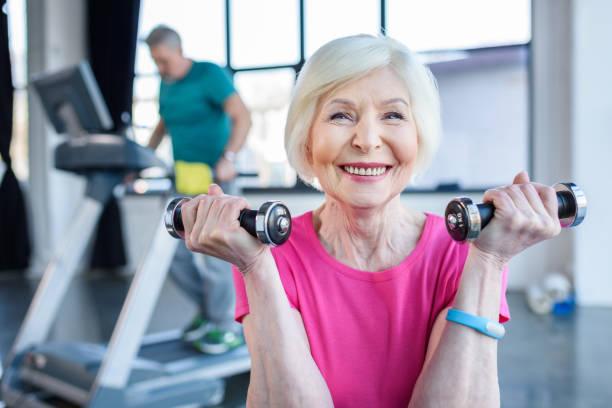 senior sportswoman sitting on fitness ball with dumbbells, sportsman on treadmill behind  in senior fitness class - foto stock