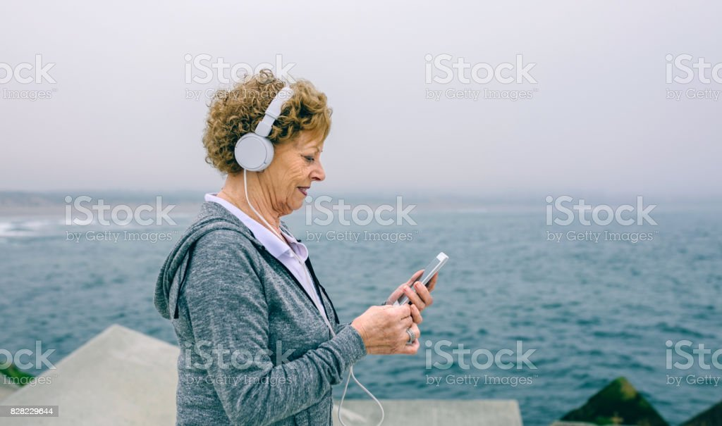 Senior sportswoman using her smartphone stock photo
