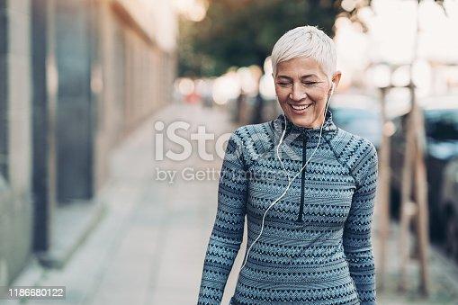Senior female athlete walking outdoors in the city