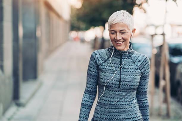Senior sportswoman walking on the street stock photo