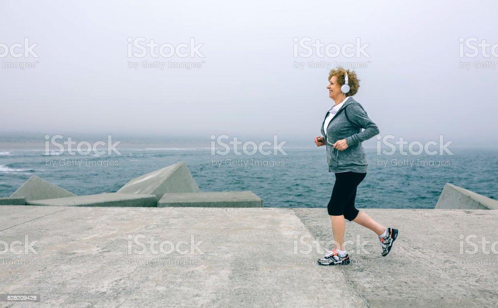 Senior sportswoman with headphones running stock photo
