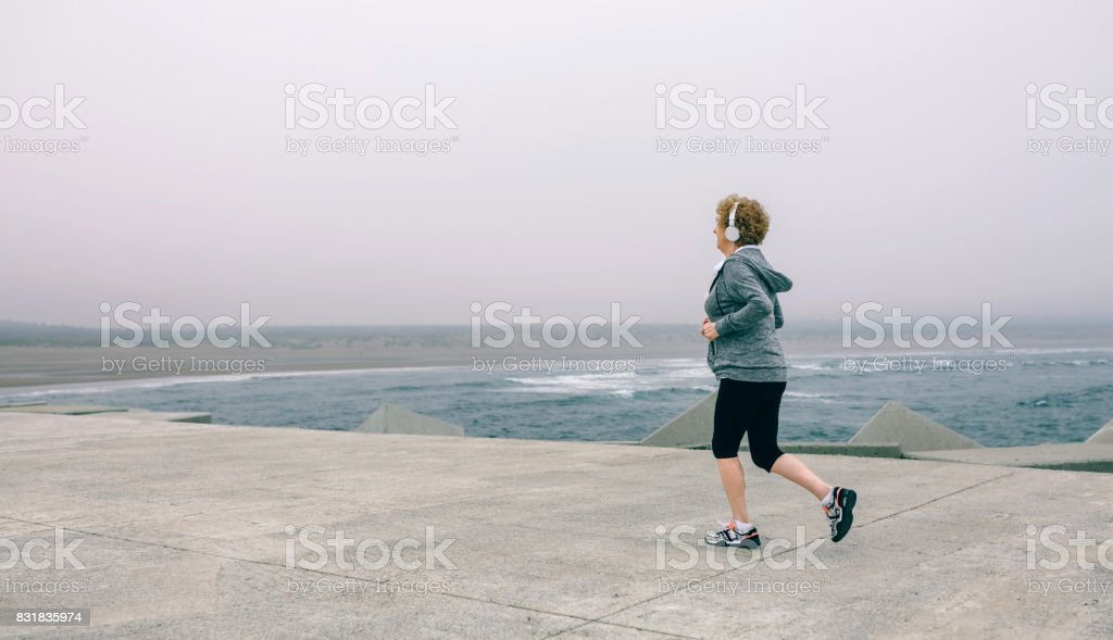 Senior sportswoman with headphones running stock photo