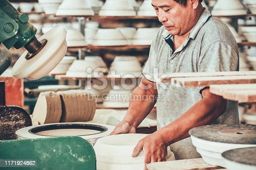 A senior man is polishing a ceramic in a factory in China.