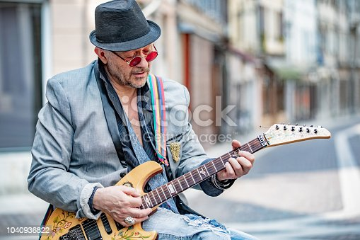 Senior Street Performer Playing Electric Guitar on City Street.