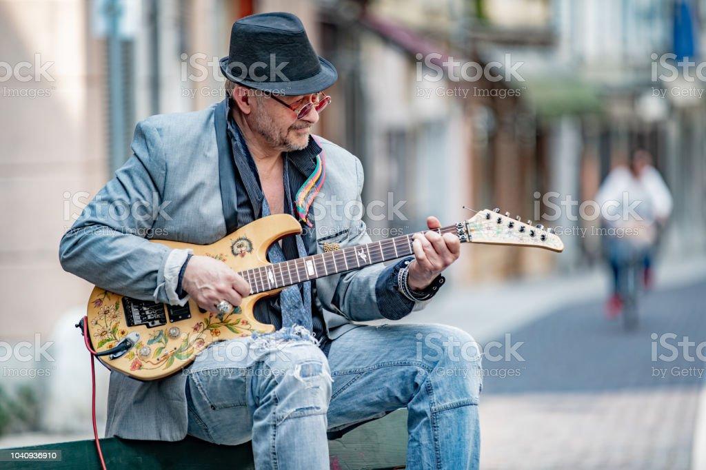 Senior Street Performer Playing Electric Guitar on City Street.