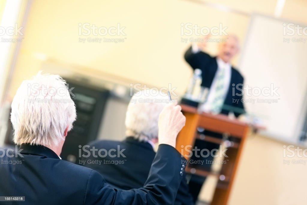 Senior student raising hand at a business seminar royalty-free stock photo