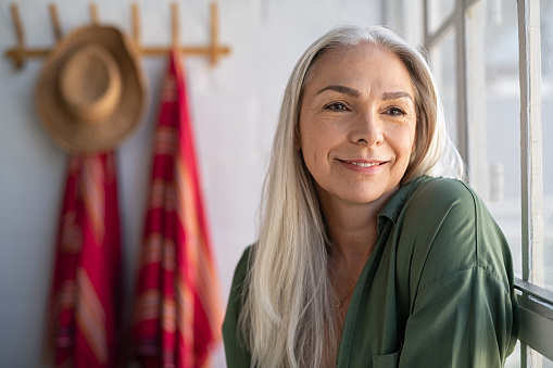 Portrait of beautiful senior woman sitting near big window at home and contemplate. Closeup face of fashionable old woman at home relaxing in living room. Mature woman thinking while looking away.