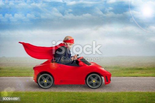 1035136022 istock photo senior superhero driving a toy sports car 500944891