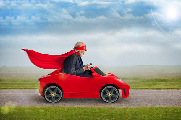 senior superheld driving einem spielzeug sports car - alten muscle cars stock-fotos und bilder