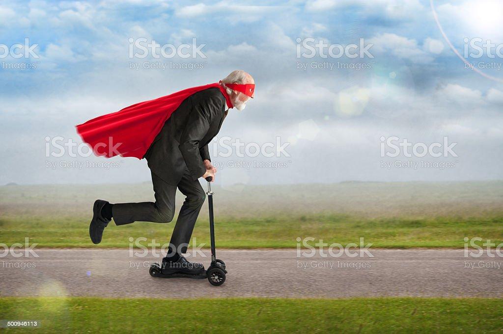 senior superhero riding a scooter stock photo