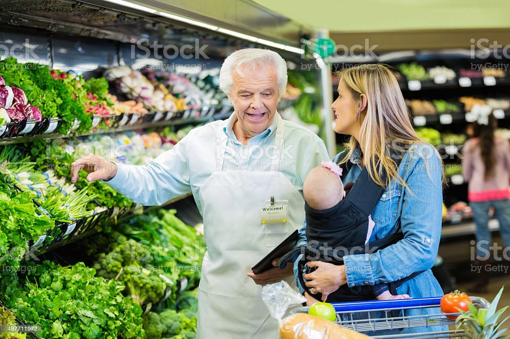 Senior supermarket employee helping young mother in produce section stock photo