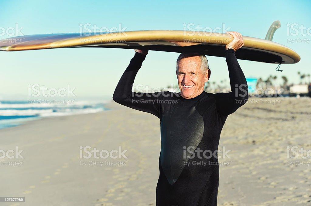 senior surfer holding surfboard on head royalty-free stock photo