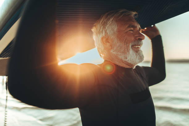 Senior surfer Photo of a senior man who still enjoys surfing and summer activities baby boomers stock pictures, royalty-free photos & images