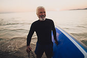 Photo of a smiling senior man who still enjoys surfing and summer activities