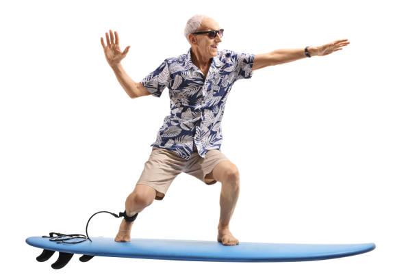 senior auf einem surfbrett surfen - dynamische posen stock-fotos und bilder