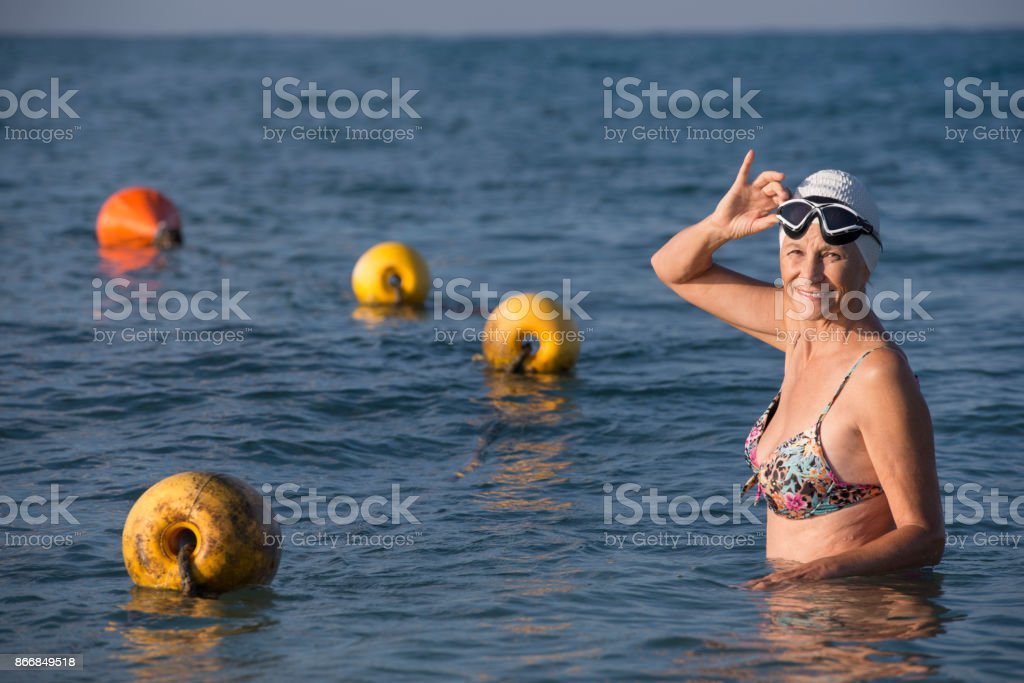 Senior swimmer female. Smiling mature woman standing on the beach sea, wearing swimming hat and goggles.Grandmother ready to morning swim. Swimming pool sea with swimming lane marker rope. 60-64 Years Stock Photo