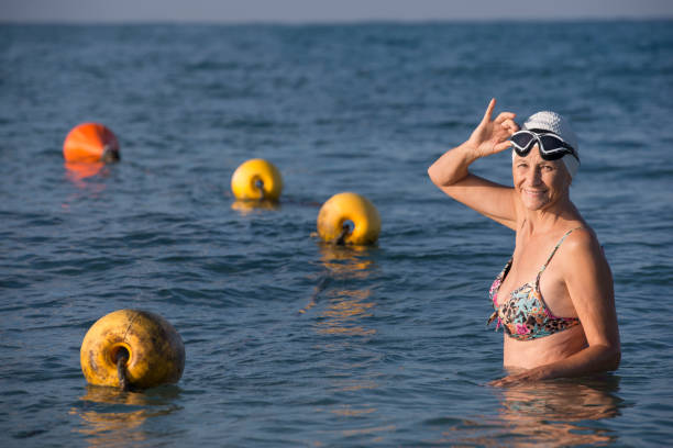 Senior swimmer female. Smiling mature woman standing on the beach sea, wearing swimming hat and goggles.Grandmother ready to morning swim. Swimming pool sea with swimming lane marker rope. middle aged women in bikinis stock pictures, royalty-free photos & images