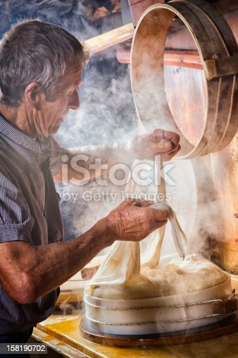 Senior Swiss Farmer making cheese the traditional way. He is tying the cheese cloth after putting the steaming fresh curd in its mold.