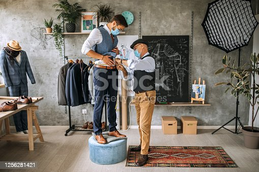 Senior tailor taking measures for a handmade suit
