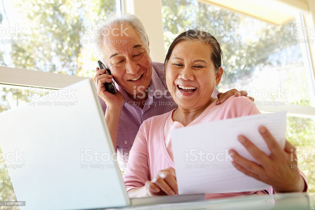 A senior Taiwanese couple happily reviewing a document stock photo