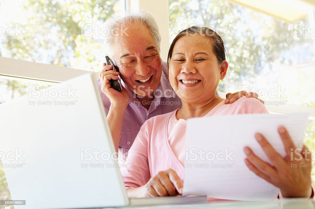 Senior Taiwanese couple working at home stock photo
