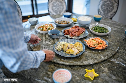 Senior Taiwanese man arranging plates of delicious food on a lazy susan in preparation for lunch at home with family.
