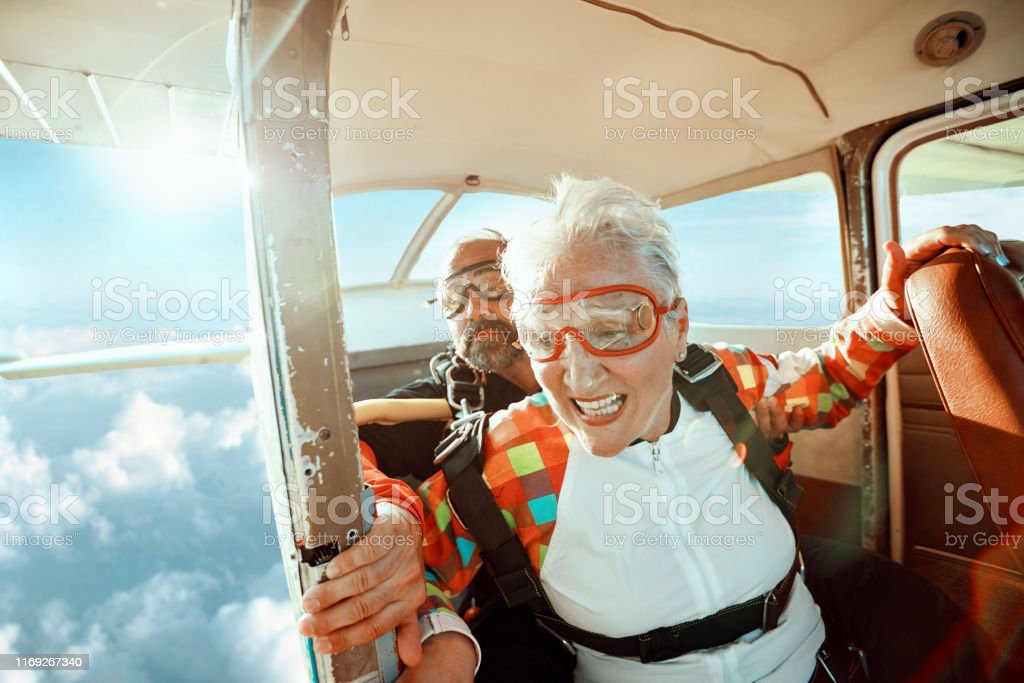 Senior tandem skydiving Close up of a senior woman and her instructor doing tandem skydiving 40-49 Years Stock Photo