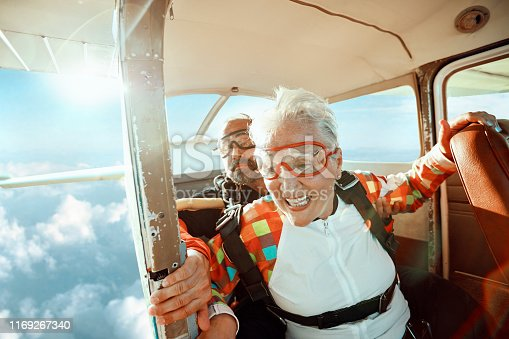Close up of a senior woman and her instructor doing tandem skydiving