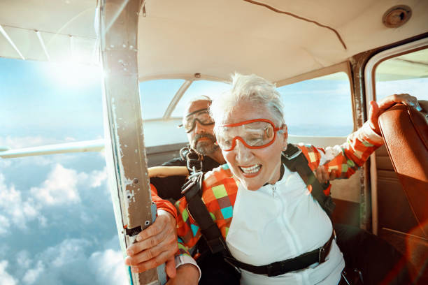 Senior tandem skydiving Close up of a senior woman and her instructor doing tandem skydiving parachuting stock pictures, royalty-free photos & images
