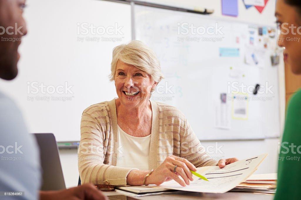 Senior teacher at desk talking to adult education students stock photo