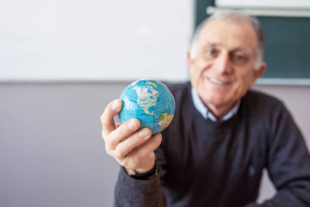 seniorenlehrerin in handglobe - kartographie stock-fotos und bilder