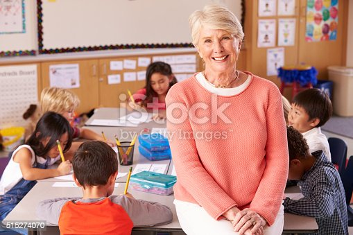 Senior teacher in classroom with elementary school kids