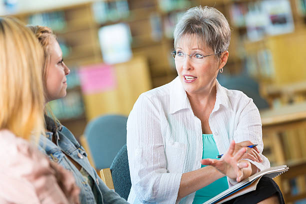 senior teacher or principle meeting with student and parent - school counselor stock photos and pictures