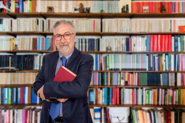 senior teacher standing holding a book in front of a bookcase - professore foto e immagini stock