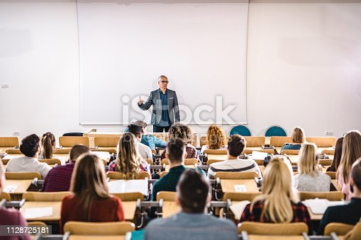Mature professor giving a lecture in front of projection screen at lecture hall. Copy space.