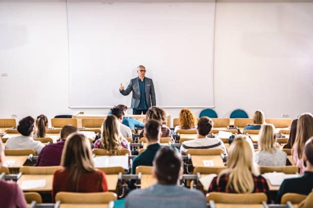 professor sênior falando para um grande grupo de estudantes universitários no anfiteatro. - universidade - fotografias e filmes do acervo