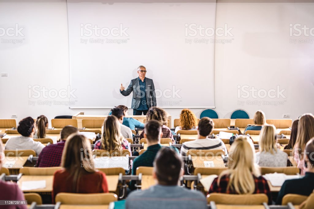 Senior teacher talking to large group of college students in amphitheater. stock photo