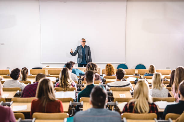 Senior teacher talking to large group of college students in amphitheater. Mature professor giving a lecture in front of projection screen at lecture hall. Copy space. public building stock pictures, royalty-free photos & images