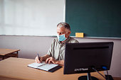 istock Senior teacher wearing a face mask during corona virus crisis 1245302465