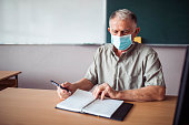 istock Senior teacher wearing a face mask 1245302466