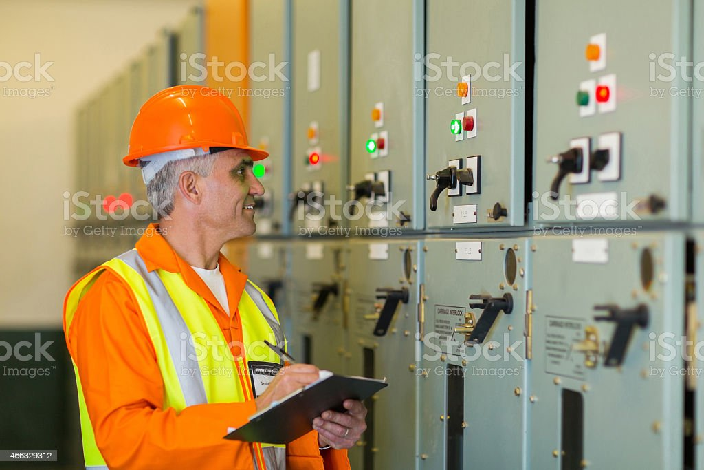 senior technician writing results of measurements stock photo