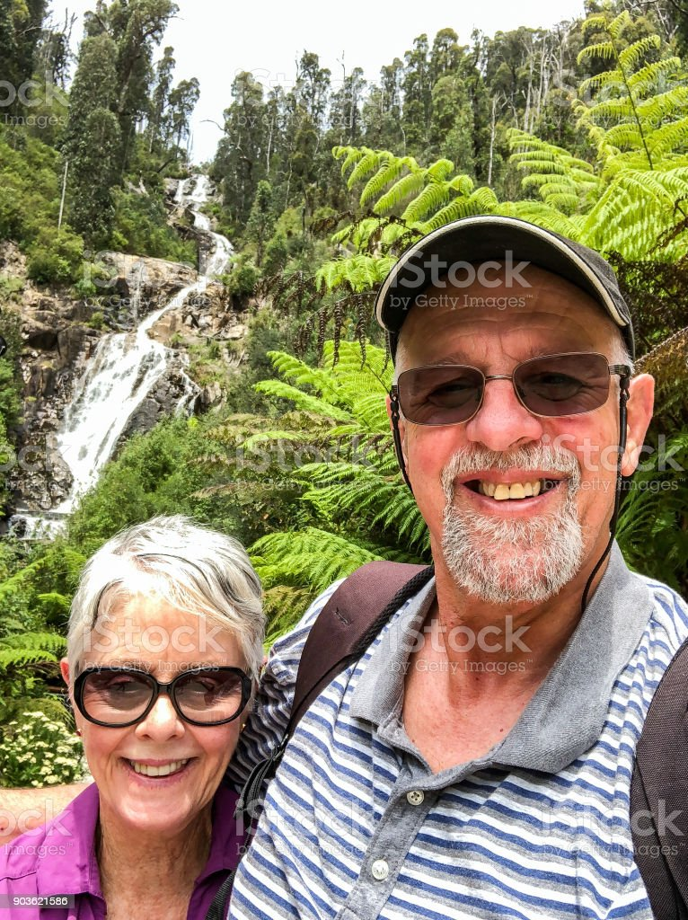 Senior Tenderness on nature walk to scenic waterfall in national park stock photo