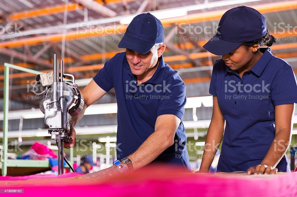 senior textile worker teaching new employee about cutting fabric stock photo