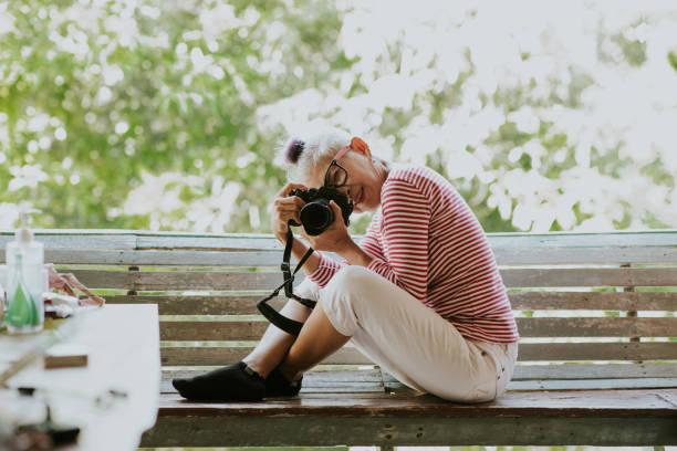 senior thai woman (60s) photographing nature. - showus стоковые фото и изображения