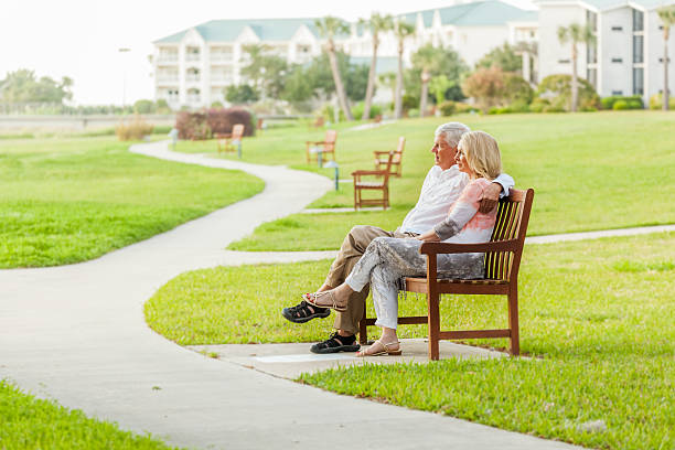 Senior Togetherness A senior couple sits on a bench at a retirement community.  They look out into the distance together. retirement community stock pictures, royalty-free photos & images
