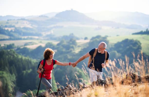 pareja turística senior con mochilas de senderismo en la naturaleza, cogidos de la mano. - excursionismo fotografías e imágenes de stock