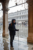 Senior tourist in flooded St Mark's Square, Venice, Italy, smiling and making the best of awful weather. Taken during the acqua alta (high tide) that floods Venice each autumn and is getting worse.